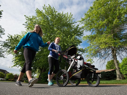 Leigh Raymer, right, walks with her son Rory (13 months) and Erica Brittingham around her neighborhood in Smyrna.   Leigh had melanoma removed last year, but it came back as a tumor in her upper thigh this past February. She is getting some of the newest treatments at Penn Abramson Center to help ward off melanoma for good.