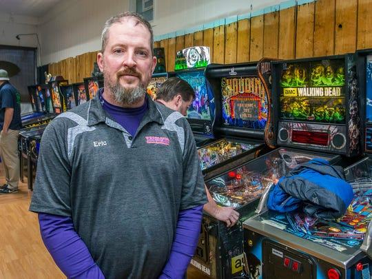 In this April 2018 photo, owner Eric Thomas, graduate of Sharon High School who served in the Marines, stands next to one of his pinball machines inside the Retro Arcade which is connected to Vaporosity in downtown Sharon, Pa. (Cory Byknish /The Herald via AP)