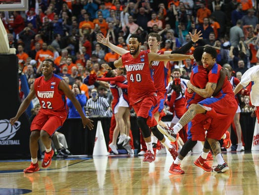University of Dayton players celebrate a 55-53  upset win over Syracuse to reach the Sweet 16.