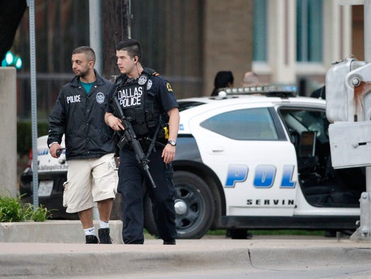 Dallas police officers walk down Belleview Street one