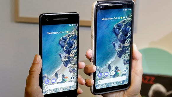 A woman holds up the Google Pixel 2 phone, left, next