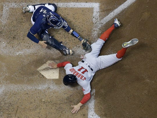 Boston Red Sox's Chase d'Arnaud slides safely past Milwaukee Brewers catcher Manny Pina during the fifth inning of a baseball game Tuesday, May 9, 2017, in Milwaukee. d'Arnaud scored on a hit by Mookie Betts. (AP Photo/Morry Gash)