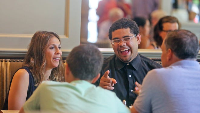 Erick, 20, a resident at the Pleasantville Cottage School, a residential treatment center run by the Jewish Child Care Association, laughs with volunteer family Liz Templeton, her husband Even, and son Matty, 15, at the Mt. Kisco Coach Diner Aug. 1, 2015. The Templeton's, who have been volunteering at the Cottage School for three years, have had a relationship with Erick for the past year and a half. They  visit with him most weeks, usually taking him off campus to restaurants, movies, and other activities.