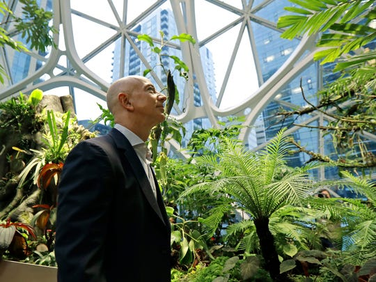 Jeff Bezos, the CEO and founder of Amazon.com, takes a walking tour of the Amazon Spheres, three plant-filed geodesic domes that serve as a work- and gathering place for Amazon employees, following a grand opening ceremony, Monday, Jan. 29, 2018, in Seattle. (AP Photo/Ted S. Warren)