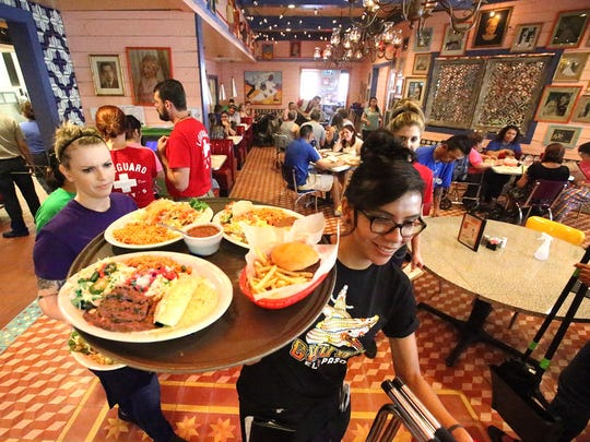 Melanie Boisselier, foreground, takes a tray full of orders to a table at the new Chuy's during its grand opening at 8889 Gateway West, Suite 1500 at the Fountains at Farah.