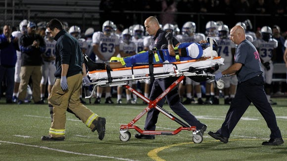 Winton Woods' Logan Day gives a thumbs-up after he was injured on a play against Bishop Chatard of Indianapolis during the third quarter at Winton Woods High School on Friday night.