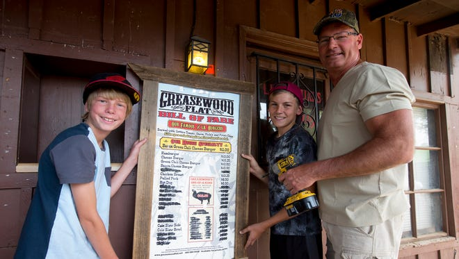 After 40 years in business Greasewood Flat in Scottsdale is closing.   James Weber, 12, poses with brother, Travis, 15, and father, David, with a sign the purchase during the bar's auction on April 11, 2015.