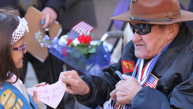 Kayla Kozell of Clifton Girl Scout Troop 6393 presents Korean War Veteran John Beagle with a Thank You card. Veterans were honored with a parade and ceremony at City Hall in Clifton. Photo taken Sunday November 8, 2015  .
