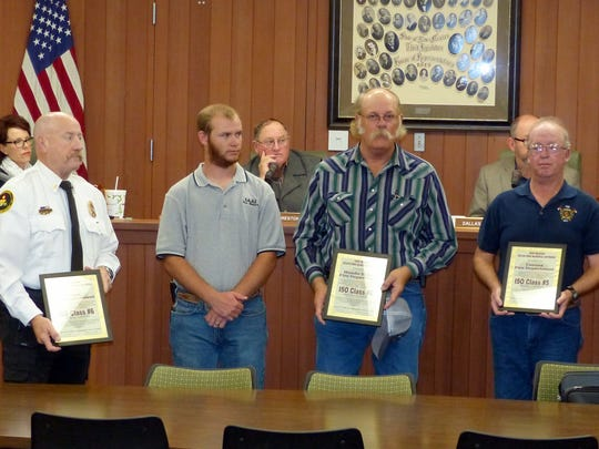 Receiving certificates of their improved ISO fire department ratings from Lincoln County Emergency Services Director Joe Kenmore, left, are from left, Aaron Griewahn, assistant Hondo fire chief; Andy Coleman, Hondo fire chief; and Brad Gage, Corona fire chief.