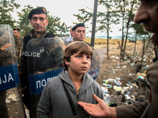 A Syrian boy waits for authorities to open the illegal