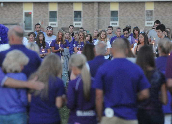 Family and friends gather for a candlelight vigil held for Cory Barron in front of Fremont Ross High School on Thursday, July 24, 2014.