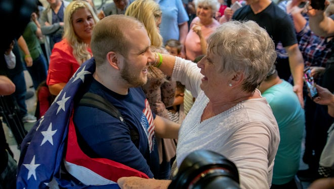 Josh Holt, left, is draped in an American flag by his grandmother Linda Holt upon returning to Salt Lake City on Monday, May 28, 2018, after he was freed this weekend after being held in a Venezuelan jail for nearly two years. He returned home to Salt Lake City on Monday night after getting medical care and visiting President Donald Trump in Washington.