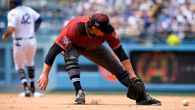 Arizona Diamondbacks starting pitcher Zack Godley, right, cannot handle a ball hit for a single by Los Angeles Dodgers' Cody Bellinger as Matt Kemp, left, advances to second during the third inning of a baseball game Sunday, April 15, 2018, in Los Angeles.