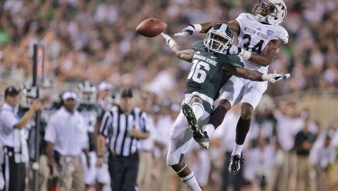 Michigan State Spartans wide receiver Aaron Burbridge (16) has the pass broken up by Western Michigan Broncos cornerback Donald Celiscar (34) during the first quarter at Spartan Stadium in East Lansing on Friday, Aug. 30, 2013.