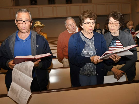 """In this Tuesday, Nov. 8, 2016 photo, Gary Brinker, front row from left, Grace Crary and Doris Kimble sing at the Ecumenical Election Day Communion Service at the Decatur First United Methodist Church in Decatur, Ga. At Decatur First United Methodist's ecumenical election night service, congregants from 13 different churches joined. Pastors spoke of unity, and the floors vibrated with """"America the Beautiful"""" from the organ pipes."""