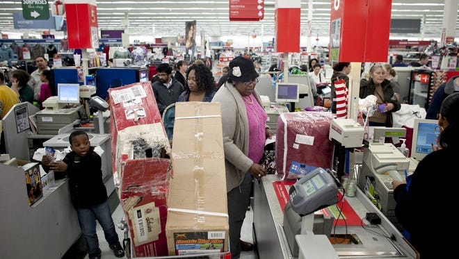 Shoppers wait in a check out line at Kmart during the Black Friday sales on November 23, 2012 in Braintree, Massachusetts.