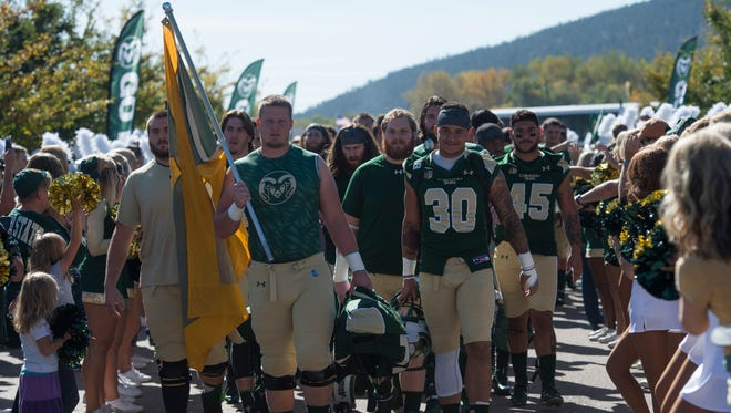 The CSU football team walks in a parade during the tailgate outside Hughes Stadium before they take on Air Force Saturday, October 17, 2015.
