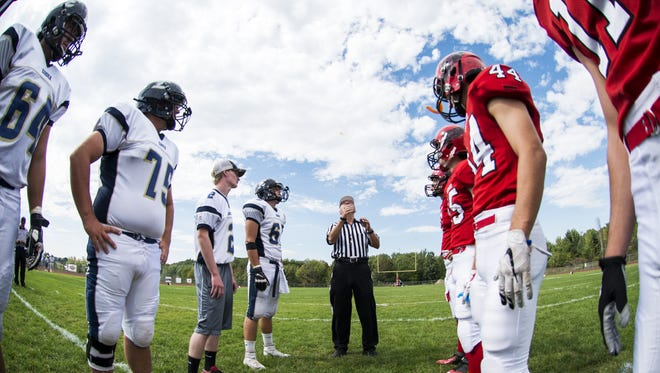 The referee fills a coin before the start of the high school football game between the Essex Hornets and the Champlain Valley Union Redhawks on Saturday afternoon.