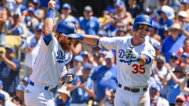 Los Angeles Dodgers left fielder Cody Bellinger (35) celebrates his third inning two run homer against the Colorado Rockies with third baseman Justin Turner (10) at Dodger Stadium.