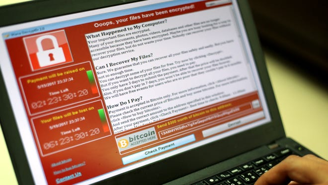 """A programmer shows a sample of a """"ransomware"""" cyberattack on a laptop. The village of Nashotah was the victim recently of a similar attack that exposed some local voting rolls."""