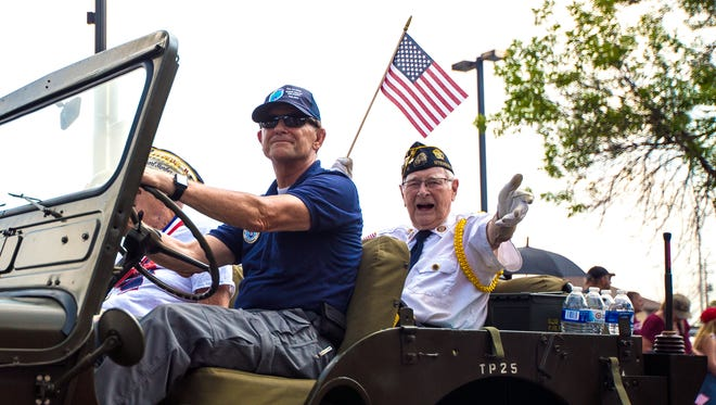 A veteran gestures to the crowd while riding in the Fourth of July parade in Stevens Point, Wis., July 4, 2018.