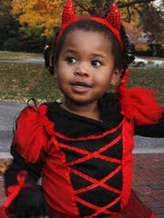 Alyssa Bowden, 2, dressed as a little devil to trick-or-treat for Halloween candy at the Governor's Residence in 2011.