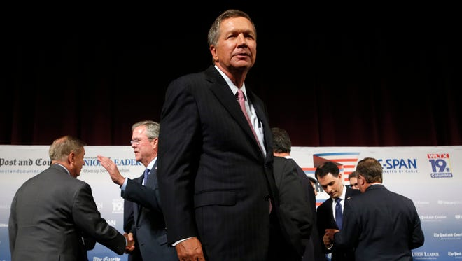 Republican presidential candidates, including Jeb Bush and John Kasich, mingle following a forum in New Hampshire on Aug. 3, 2015.