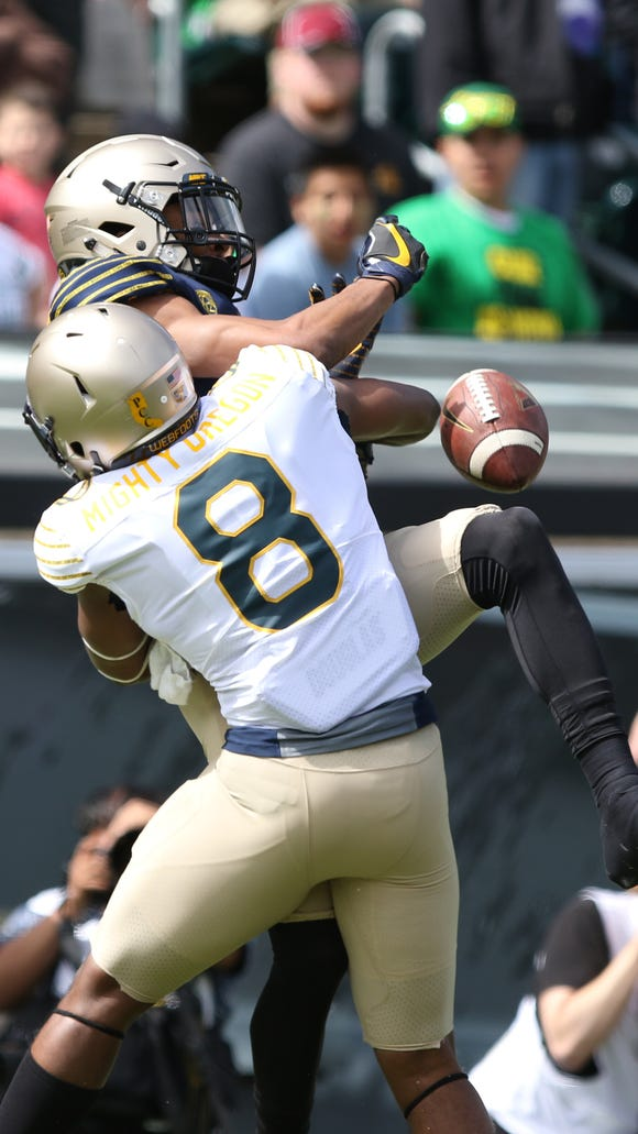Reggie Daniels (No. 8) and Darren Carrington collide during the Ducks spring game on Saturday, April 30, 2016, at Autzen Stadium in Eugene, Ore.
