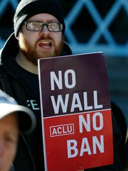 "Eric Buerk, of Seattle, holds a sign that reads ""No"