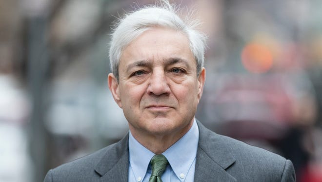 Former Penn State president Graham Spanier walks to the Dauphin County Courthouse in Harrisburg on Friday before the jury returned a split verdict in his case.