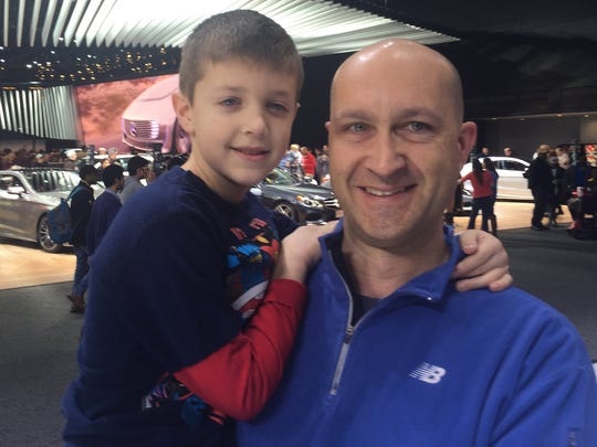 Mike Bangs, 45, of Allen Park, and his son Tyler, 6, visit the 2015 North American International Auto Show in Detroit Monday. Bangs said he would not get a car loan that lasts 7 years.