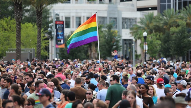 People gather at a vigil for the victims of a mass shooting at the Pulse nightclub, at Dr. Phillips Performing Arts Center in downtown Orlando, Fla., Monday, June 13, 2016.
