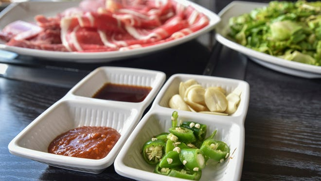 Bold flavors accessorize a meal at Mi Dahm Korean restaurant in Upper Tumon. The foreground dishes contain, clockwise from left: mixed chili paste with fresh-ground garlic, sesame oil with salt and pepper, fresh garlic cloves, and hot peppers.