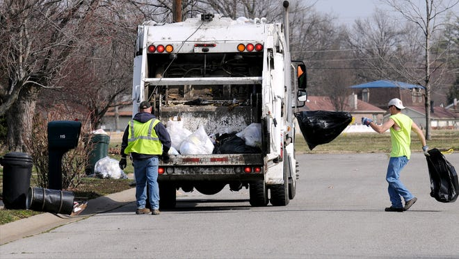 Slinging bags a trash into the truck, Henderson sanitation workers Robbie Proctor (L) and Josh Hitt make their way through a local subdivision in this file photo from March, 7, 2012.