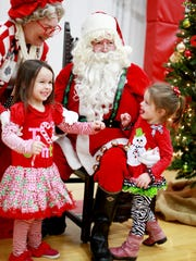 Alexandra McMichael, 4, and sister Zeva, 2, of Staunton meet Santa and Mrs. Claus at the WTON/Staunton Rotary Children's Christmas Party on Saturday, Dec. 13, 2014 at the Gypsy Hill Park Gym.
