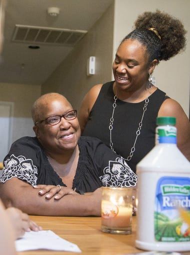 Donna (left) and Sharicka McHenry talk to their adopted children during a dinner. McHenry, always wanted a family, so they brought together four siblings scattered to different foster homes.