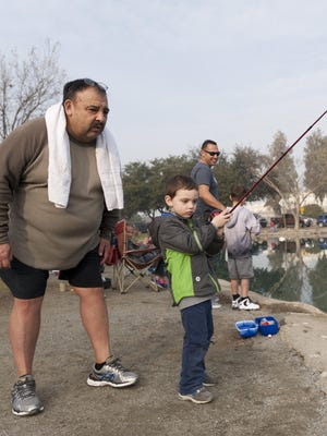 Jose Salazar, left, watches his grandson John Schulz, 3, reel in his second catch of the day during Visalia Parks and Recreation's annual fishing derby.