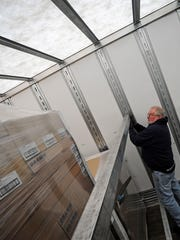 Warehouse worker Randy Dolgner of Sheboygan creates a wall inside a truck to limit shifting during transit in a trailer at Wisconsin Nationwide in Two Rivers.