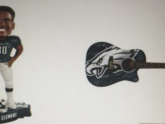 A $35 Corey Clement bobblehead stands next to a $3,000 guitar signed by the Philadelphia Eagles running back and other teammates at the Birds' online store.