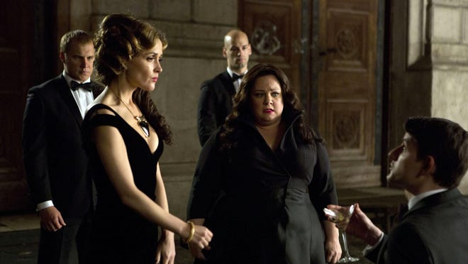 "Melissa McCarthy (second right) infiltrates an arms dealing ring led by Rose Byrne (left) in a scene from the film ""Spy."""
