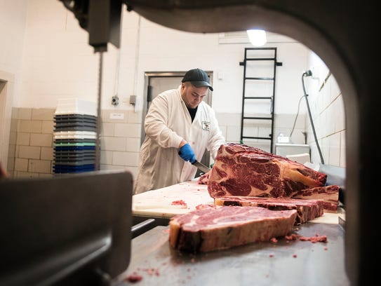 Taylor Kuhns, lead retail butcher, slices meat behind