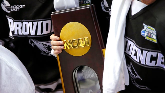 Apr 11, 2015: Providence College Friar players hold the trophy after defeating the Boston University Terriers 4-3 in the championship game of the Frozen Four college ice hockey tournament at TD Garden.