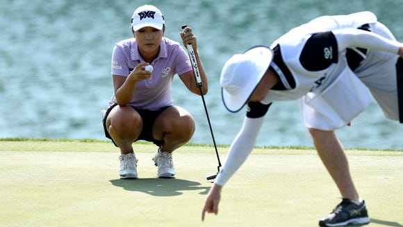 Lydia Ko works with her caddie on the 18th green during