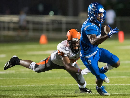 Dana Brown of Barron Collier escapes the grasp of Gedeon Dumesyeux of Lely during the game at Barron Collier Friday night, September 23, 2016. Photo by Darron R. Silva