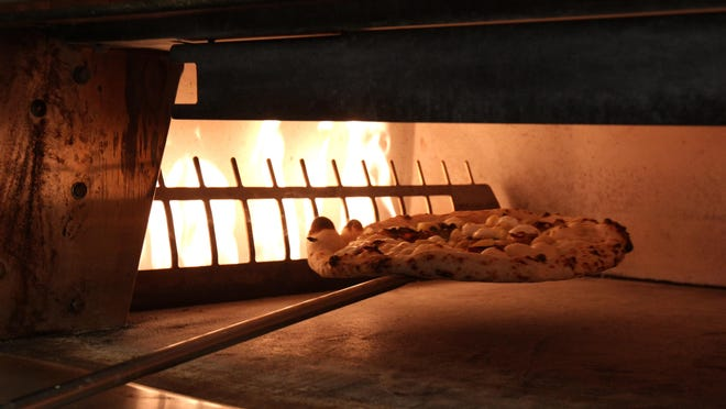 Steve Mignogna of Ocean Grove, co-owner of Talula's, makes a pizza inside his Cookman Avenue restaurant.