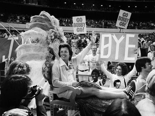 """FILE - In this Sept. 20, 1973, file photo, . Billie Jean King waves to crowds at the Astrodome in Houston, Texas, as she is borne onto the crowd on a multi-colored throne carried by four men for her match with Bobby Riggs. The story of the early days of the tour and King's fight for equal prize money is chronicled in the movie """"Battle of the Sexes,"""" which opened nationwide on Friday. (AP Photo/File)"""