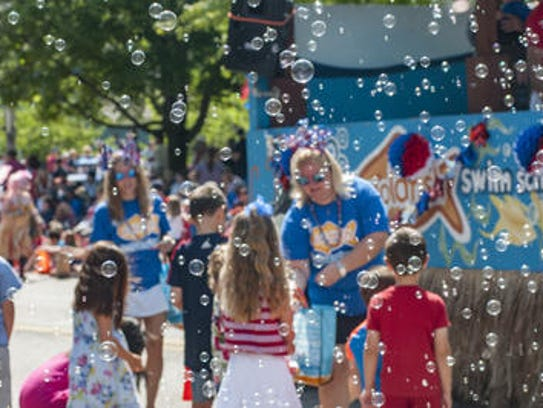 Paradegoers are surrounded by soap bubbles near the