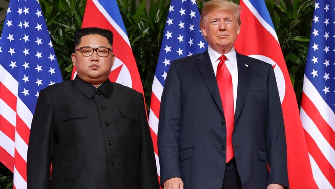 President Donald Trump stands with North Korea leader Kim Jong Un for a photograph at the Capella resort in Singapore.