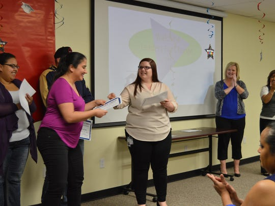 Emily Garcia from Parenting Network hands out graduation certificates while facilitators Darcy Massey and Debbie Benavente clap for their graduates.