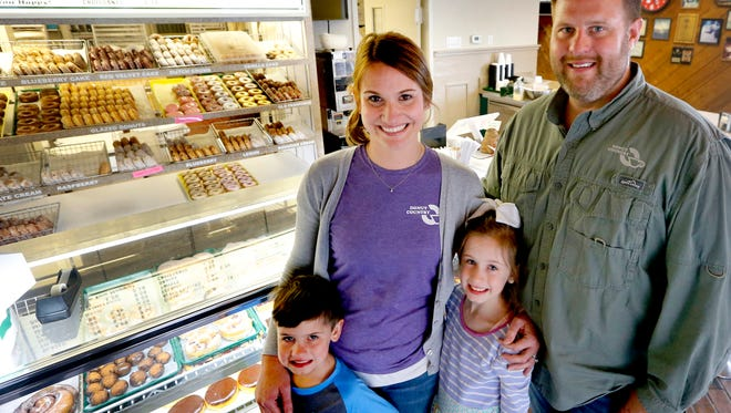 Donut Country owners Kristy and Bo Davis stand with their children Bennett, 5, and Hadley, 8. The shop is vying for top spot in the Sweetest Bakery in America contest, which is going on through July 31.